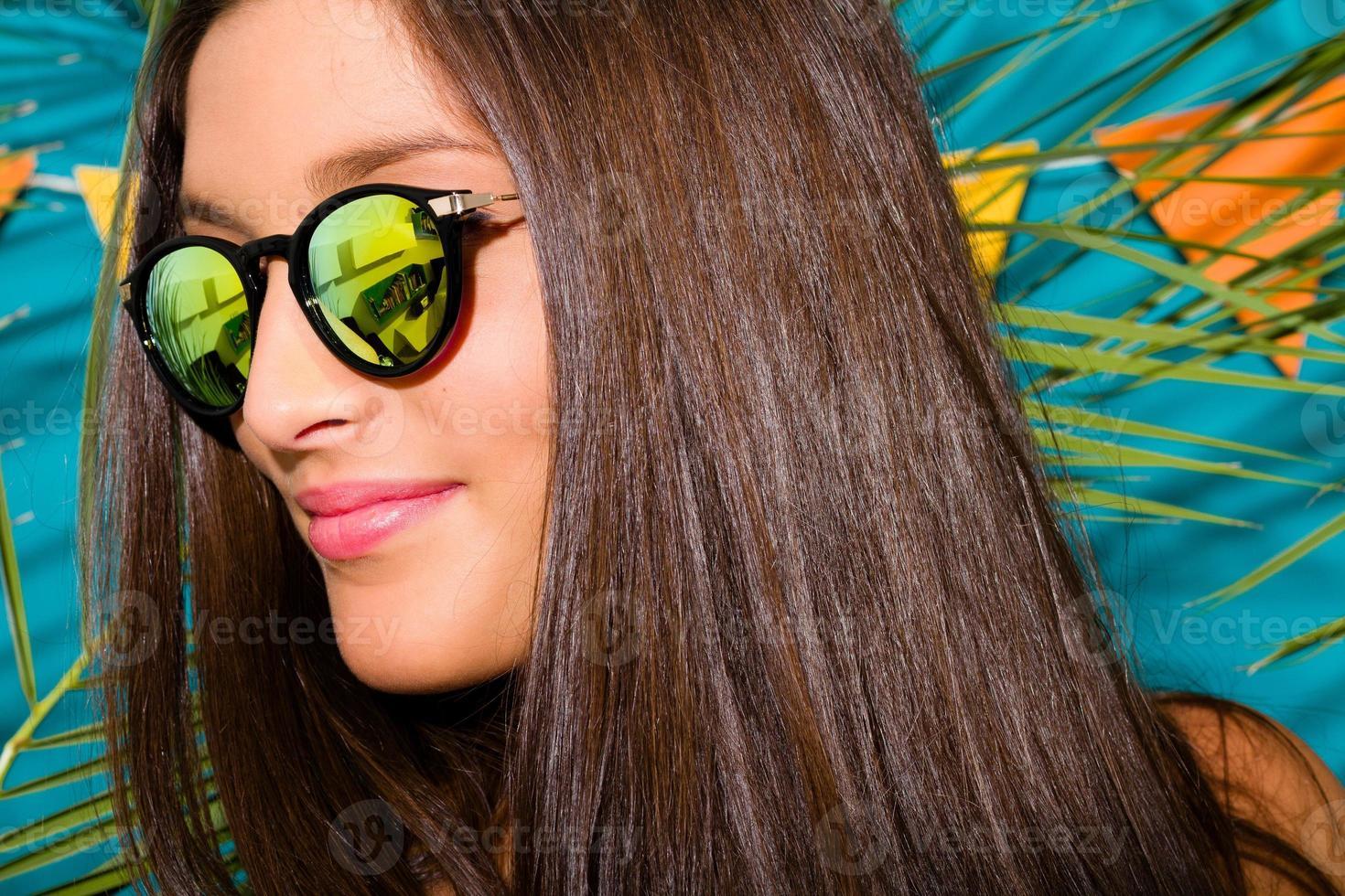 Chica con gafas de sol de espejo sobre un fondo con hoja de palma foto