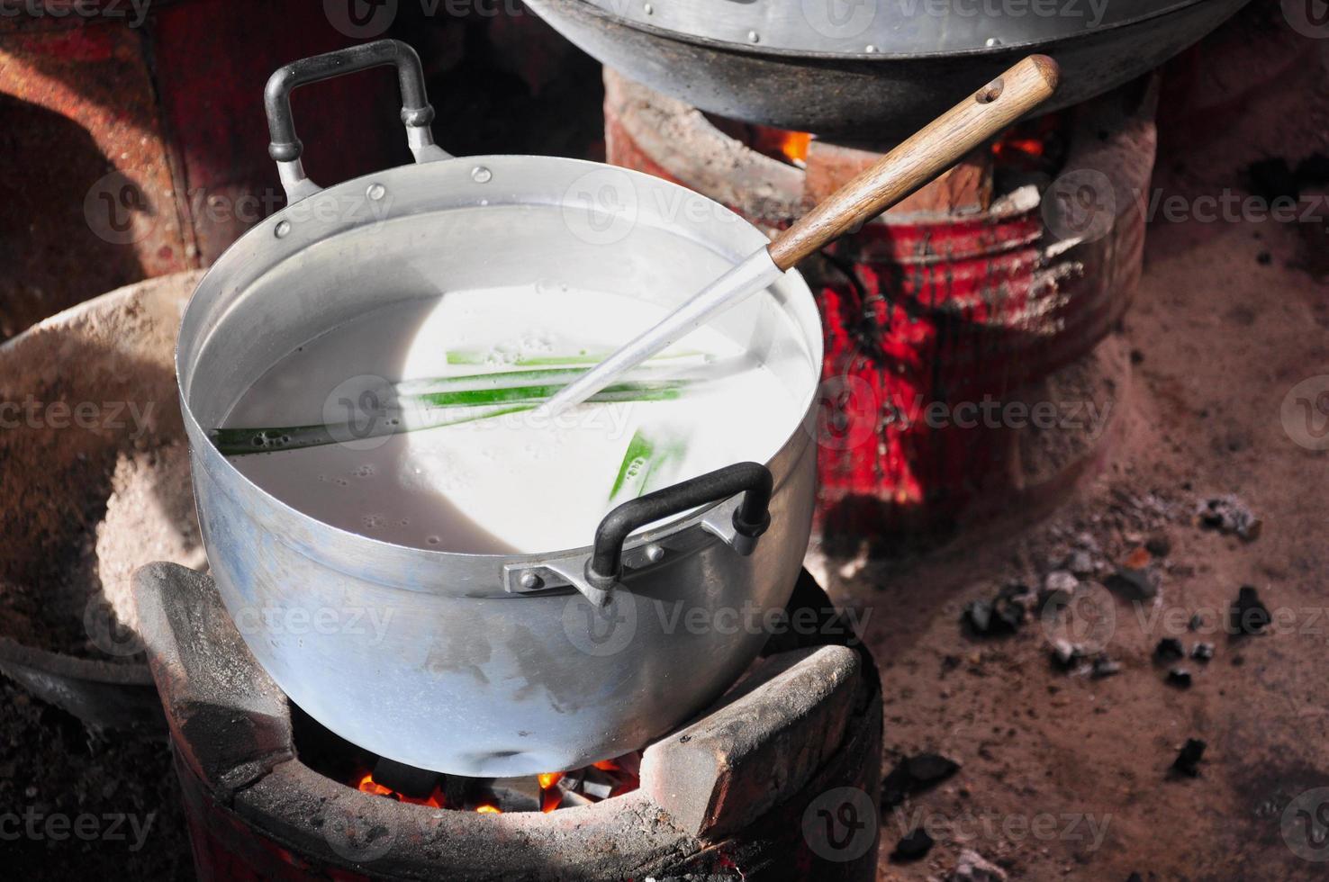 cocinar leche de coco en una olla, hirviendo foto