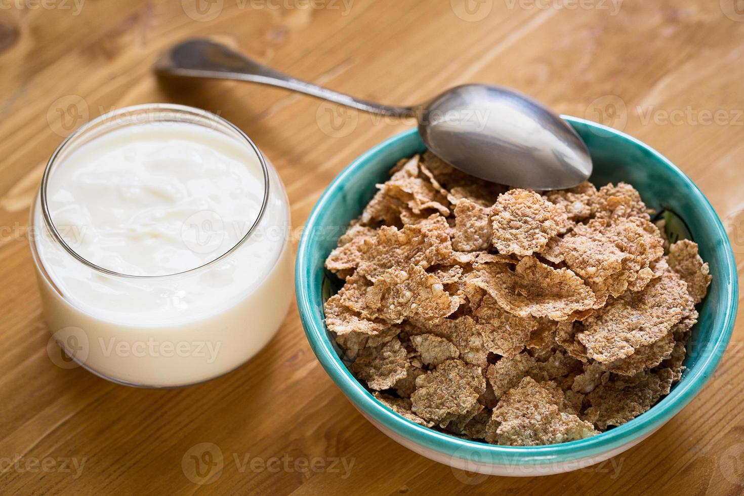 Copos de trigo deliciosos y saludables en un tazón con yogur foto