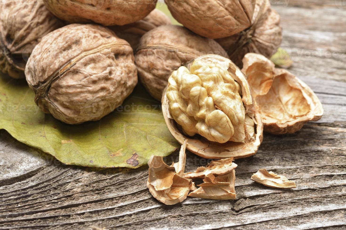 Walnut kernels and whole walnuts on rustic old wooden table photo