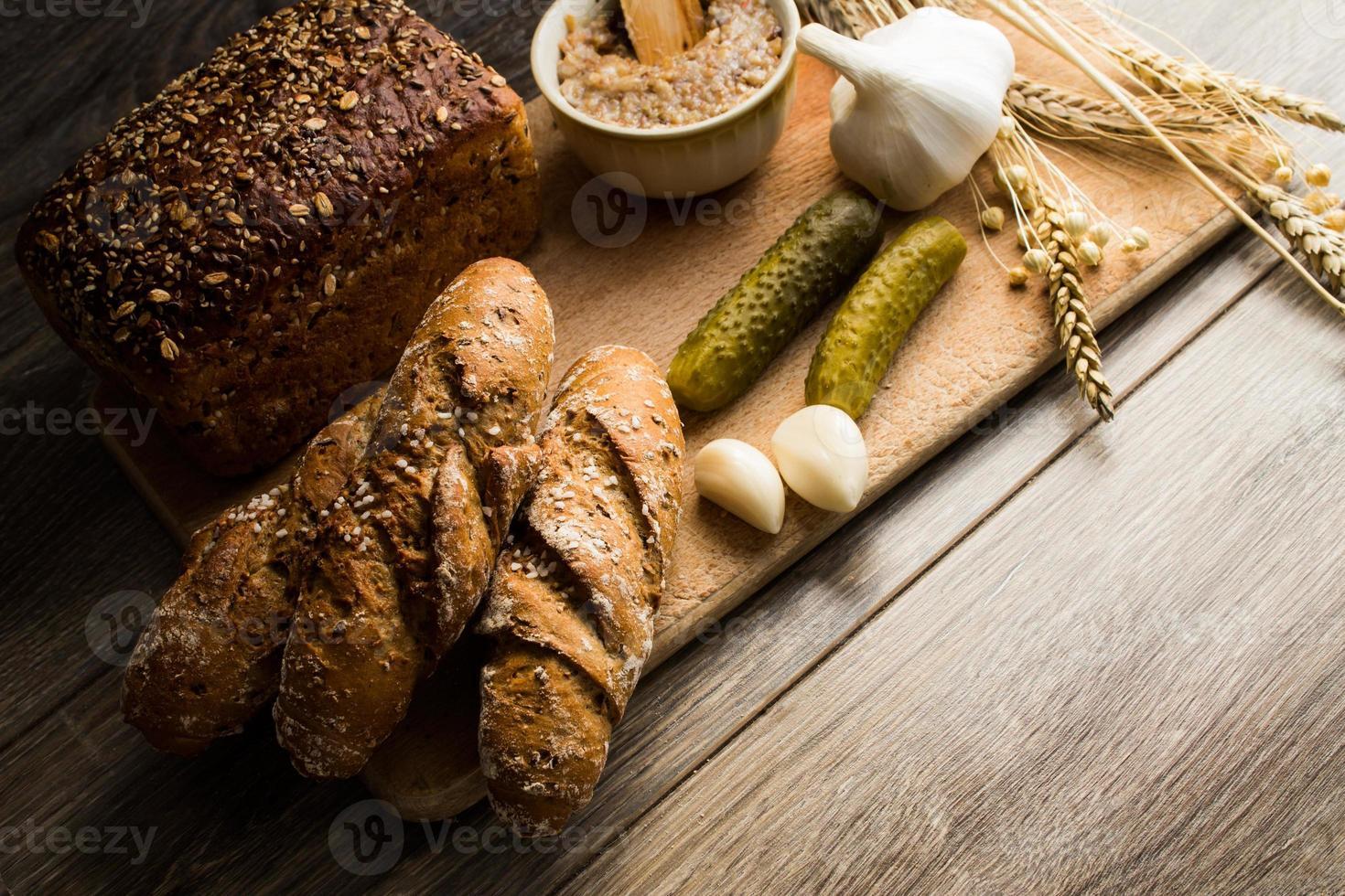 Manteca de pan y encurtidos sobre tabla de cortar de madera vieja foto