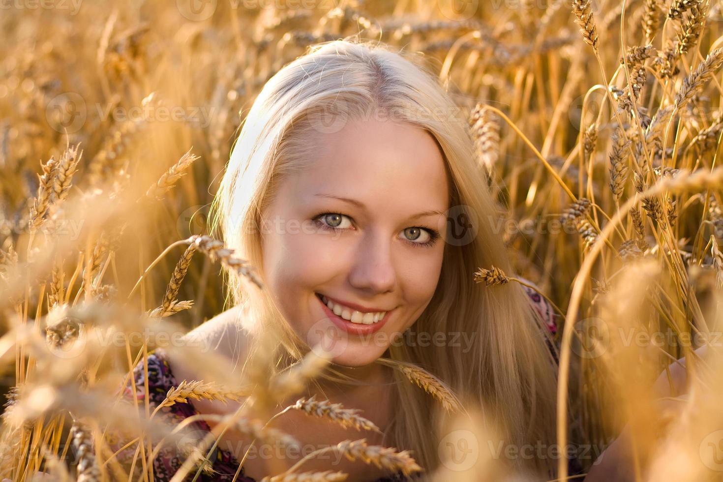 Hermosa mujer rubia sonriendo en el primer plano del campo de trigo foto