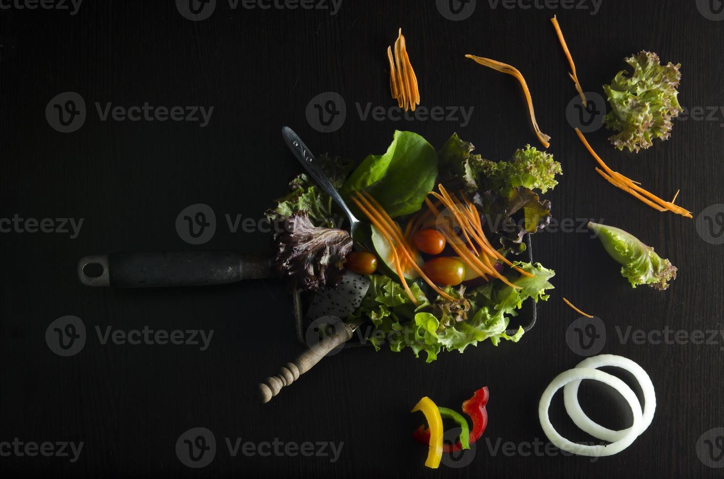 Preparación de ensalada de verduras sobre fondo negro foto