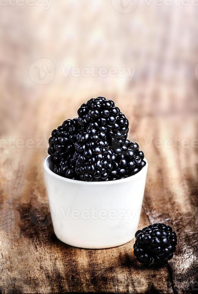 Fresh Blackberries in a white bowl on  wooden table closeup photo