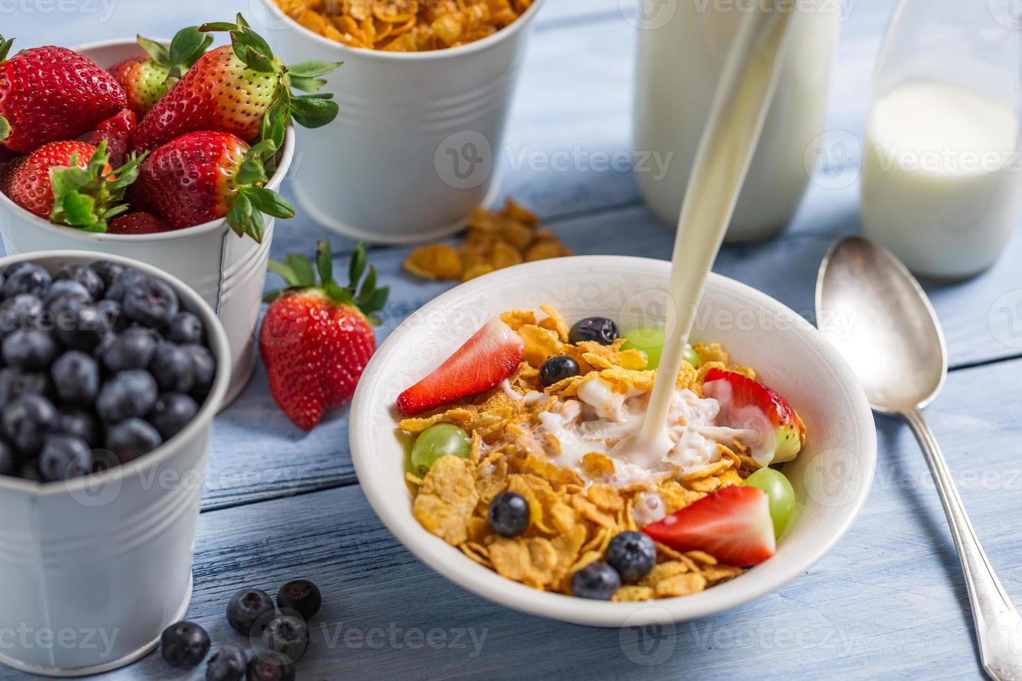 vertiendo leche en copos de maíz con frutas foto