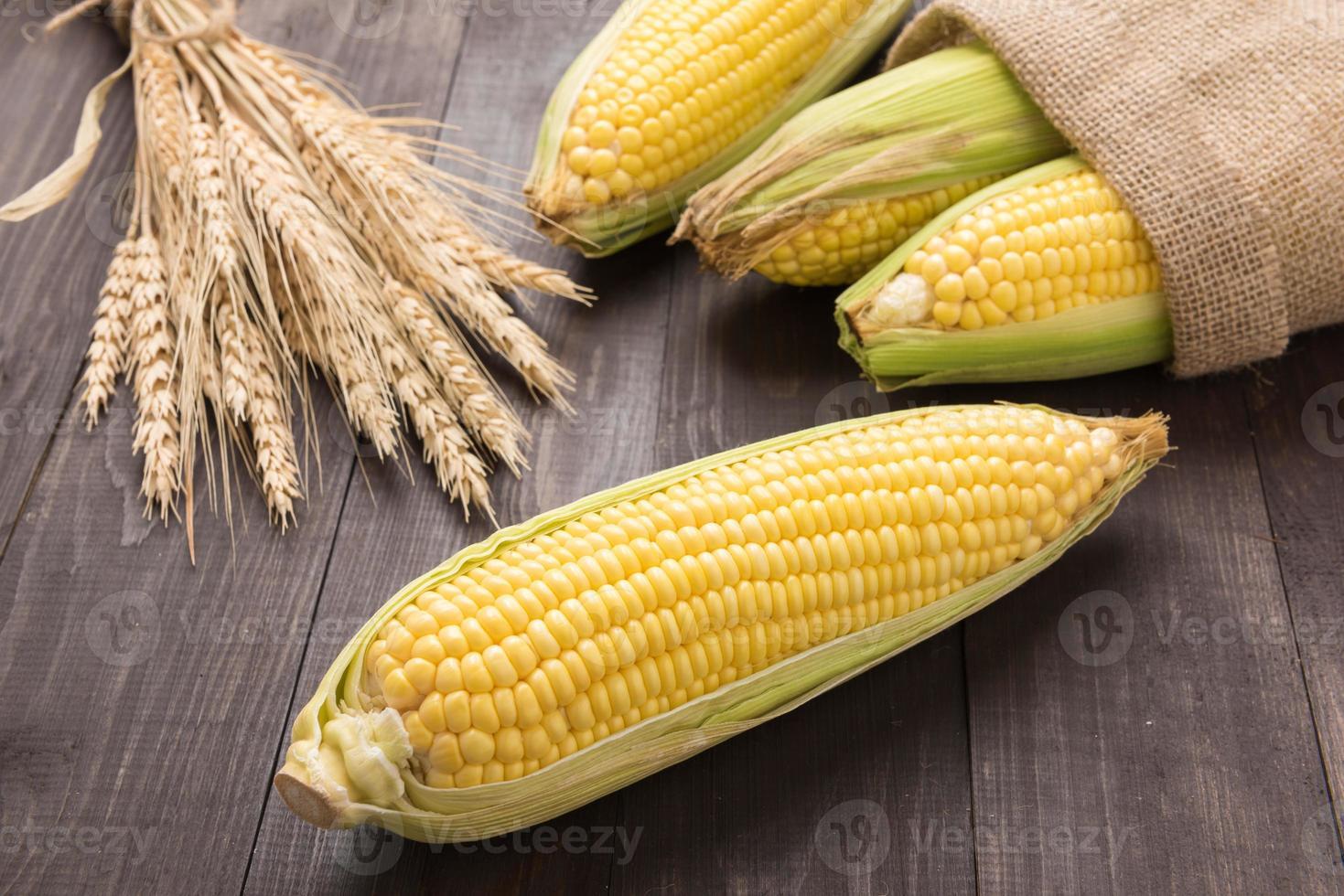 Fresh organic yellow sweet corn on wooden table photo