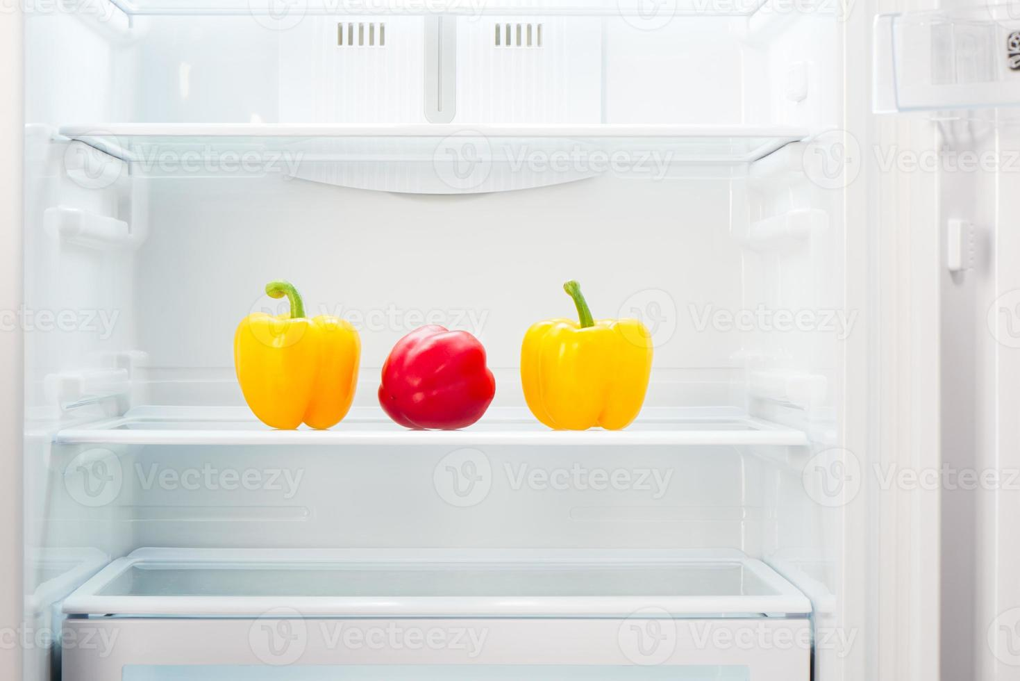 Two yellow with one red peppers on shelf of refrigerator photo