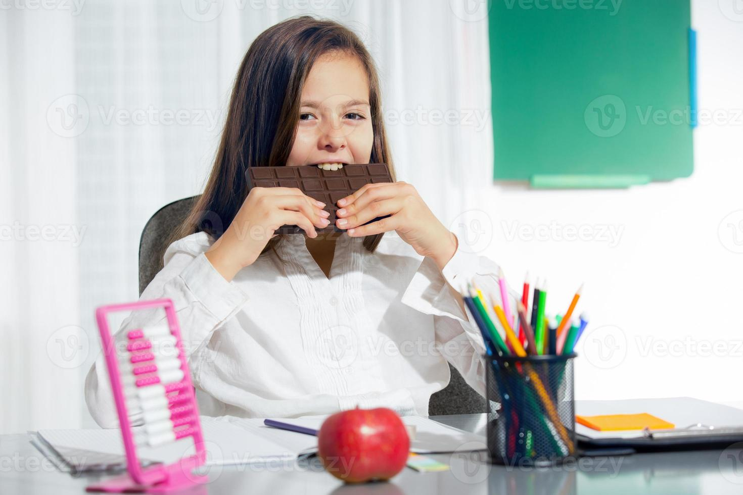 Little girl eat chocolate at room photo