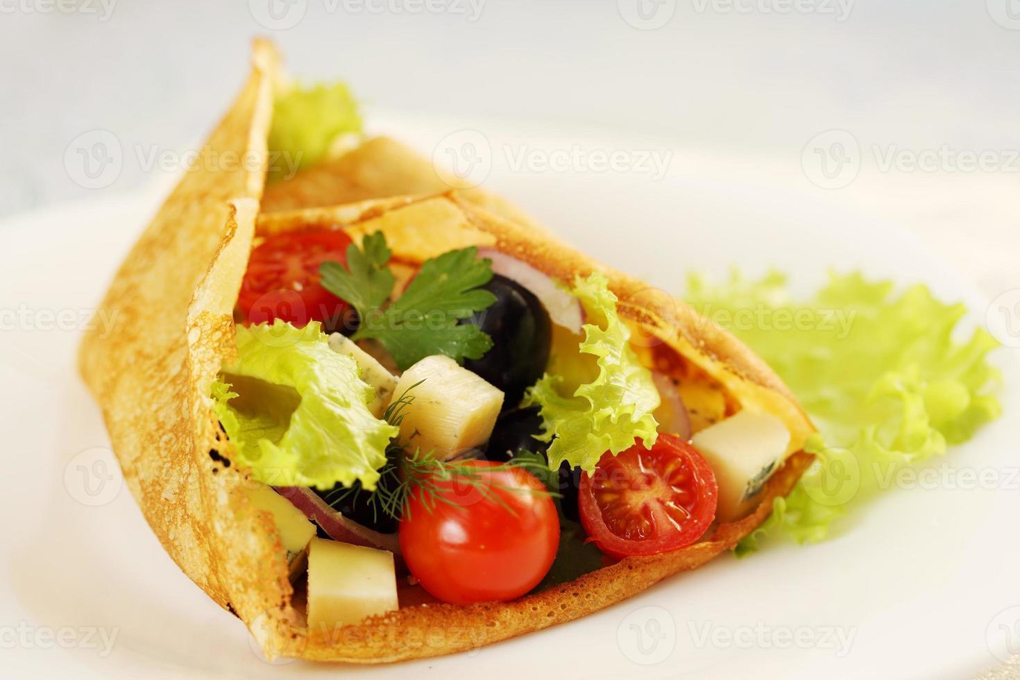 Pancake stuffed with salad photo