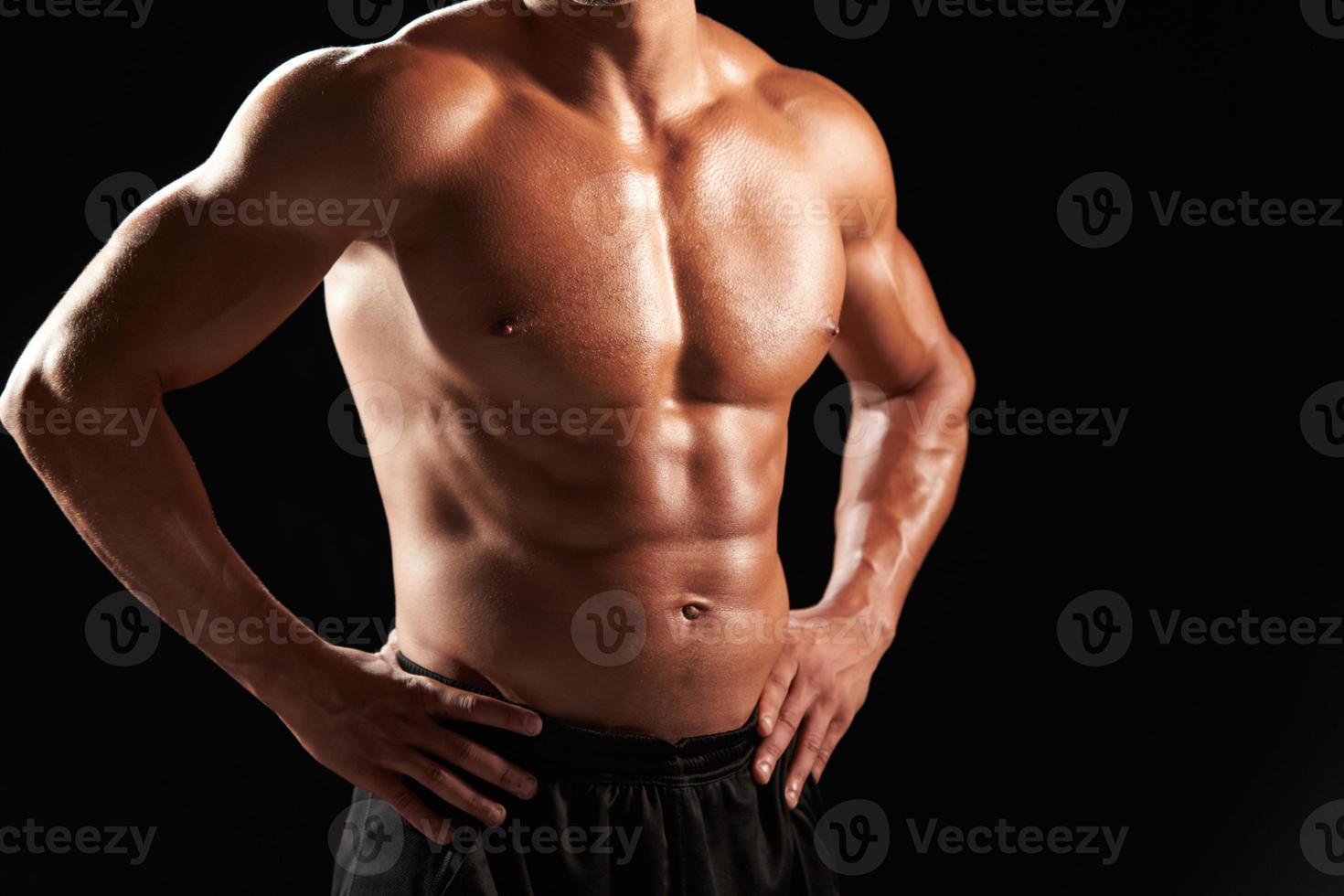 Culturista masculino con el torso desnudo con las manos en las caderas, cultivo foto