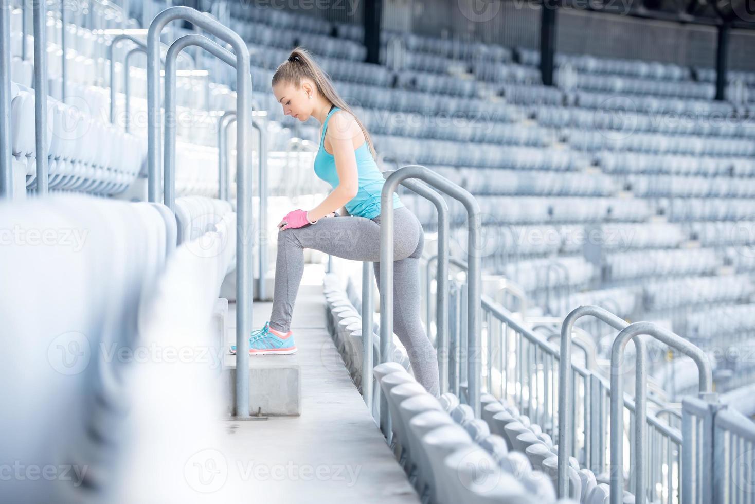 Entrenador de fitness femenino preparándose para entrenar, estirar y hacer sentadillas foto