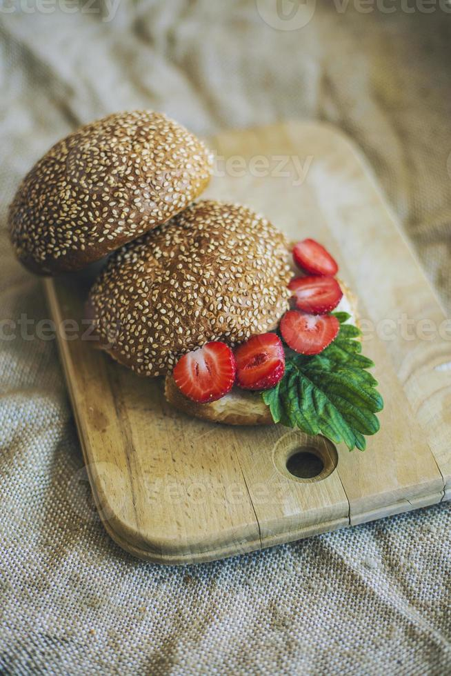 Breakfast with berries and a roll on a wooden Board photo
