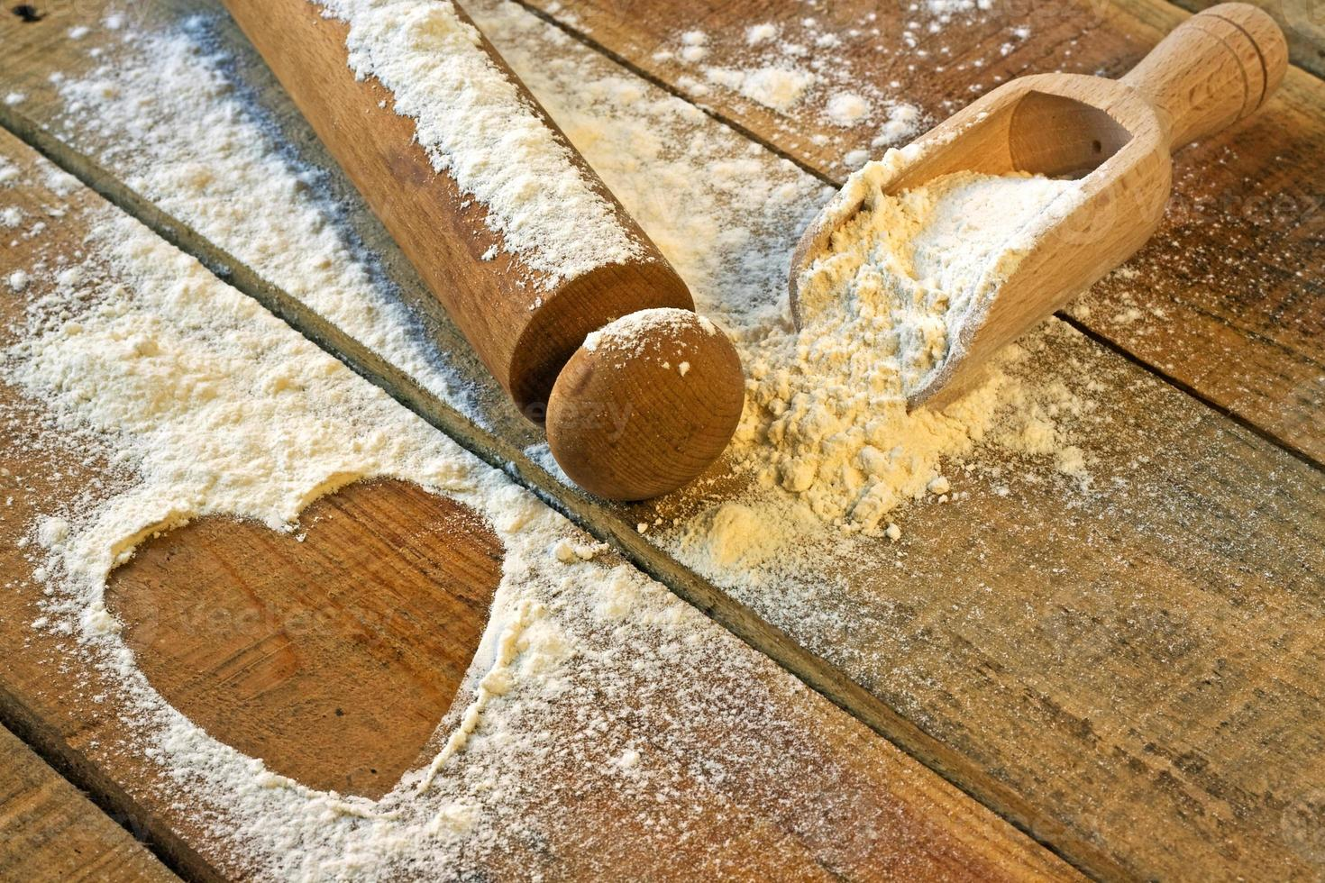 flour, rolling pin and heart with wood background photo