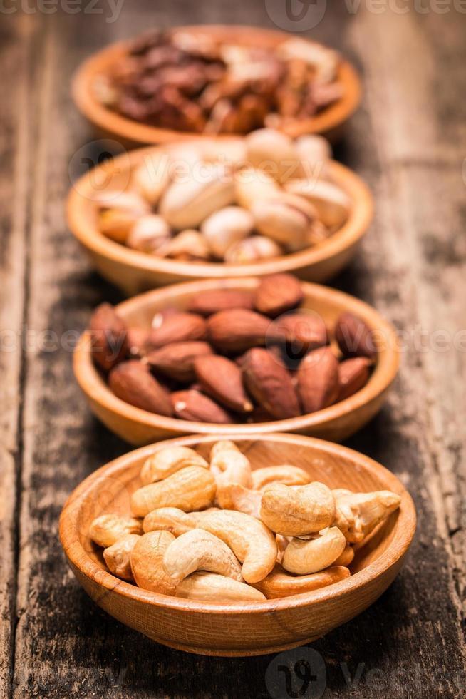 mezclar nueces en la mesa de madera, comida vegana saludable. foto