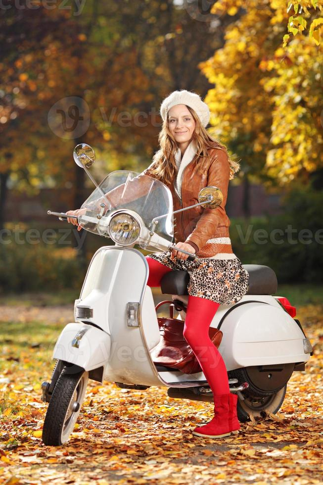 Portrait of beautiful young woman on scooter photo