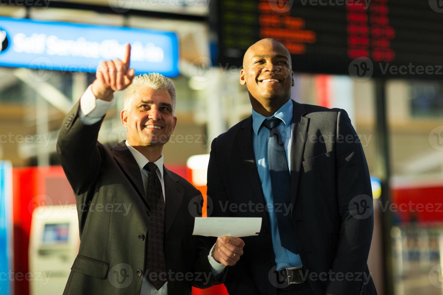 business travellers pointing at flight information board photo