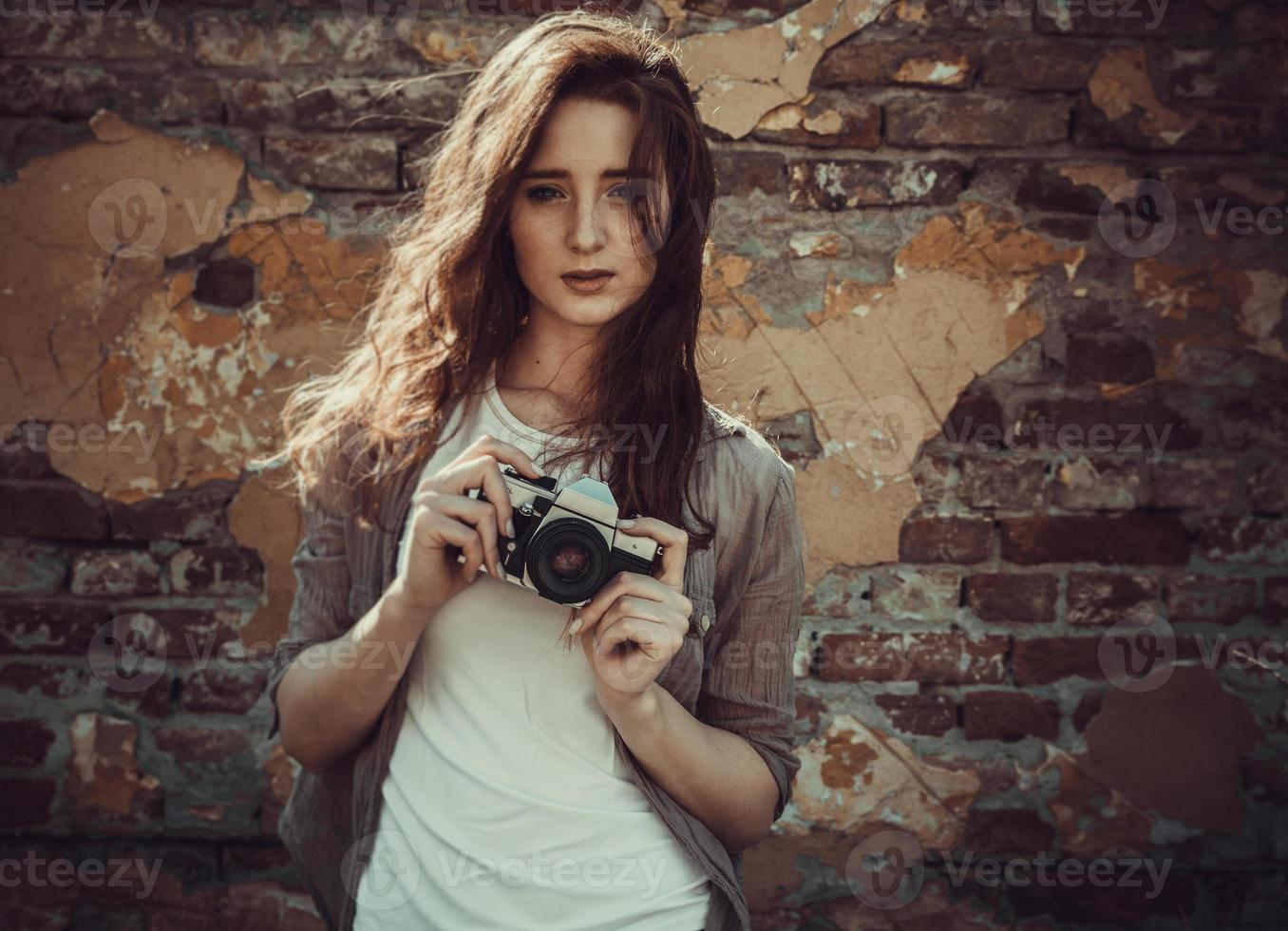 Woman standing by the wall and holding retro camera, photo