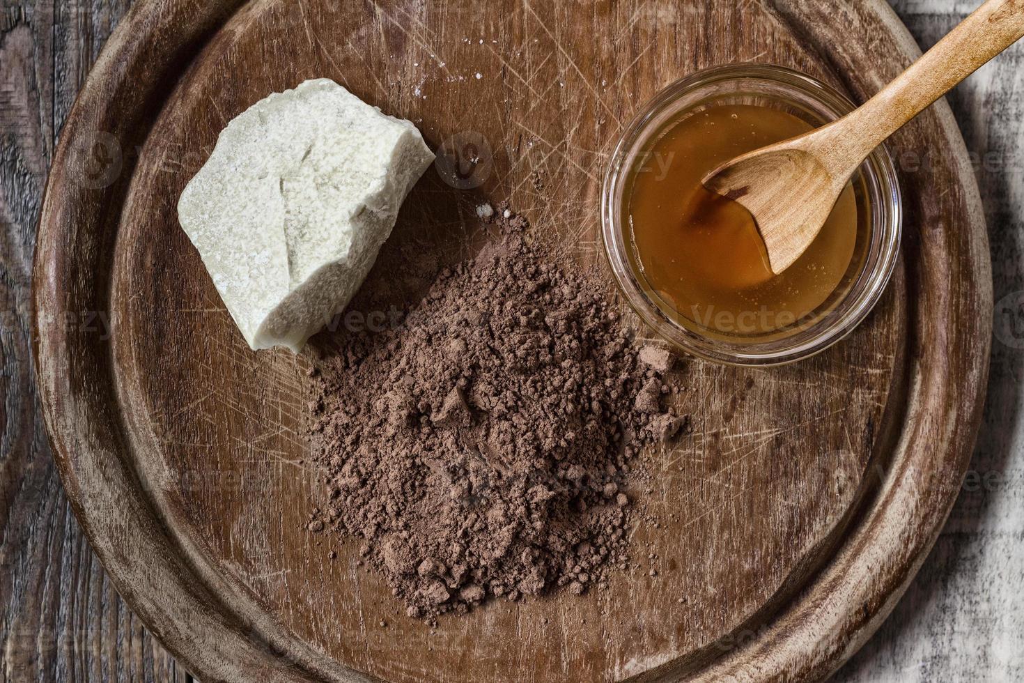 Manteca de cacao, cacao en polvo y miel sobre fondo de madera grunge foto
