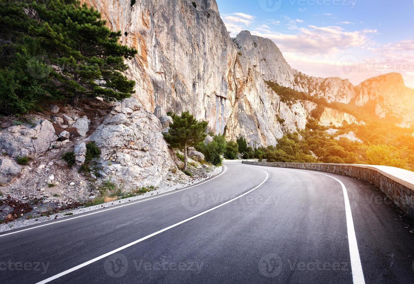 Carretera asfaltada en bosque de verano al atardecer. montañas de Crimea foto