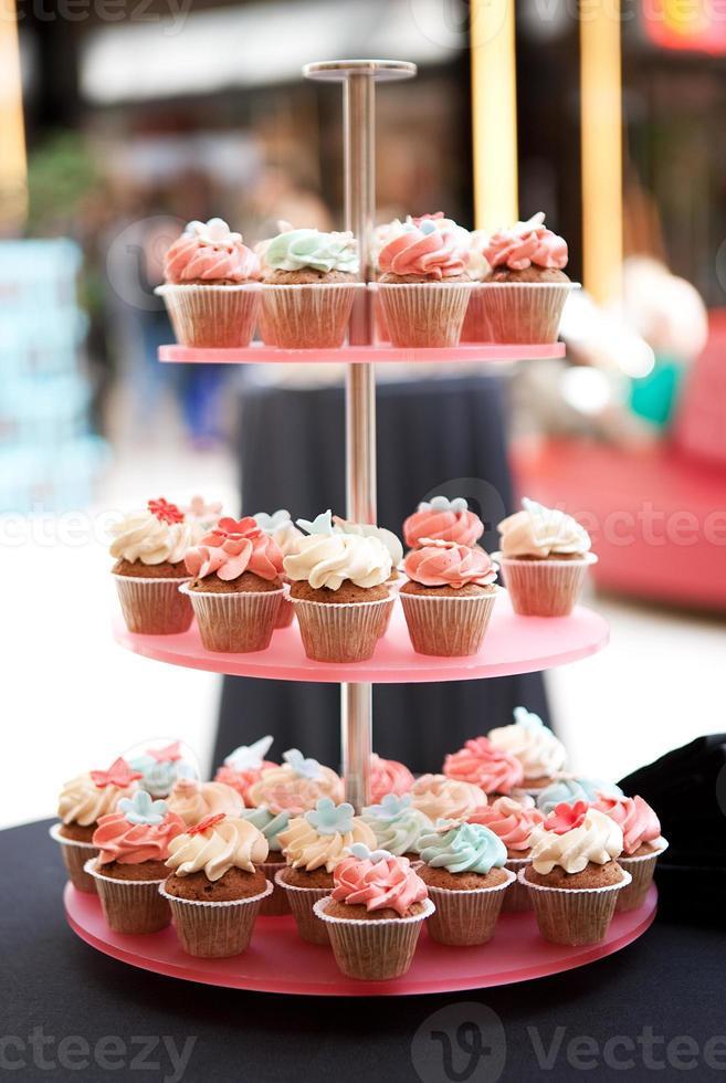 Torre de cupcakes con guarnición de guinda sobre fondo borroso foto