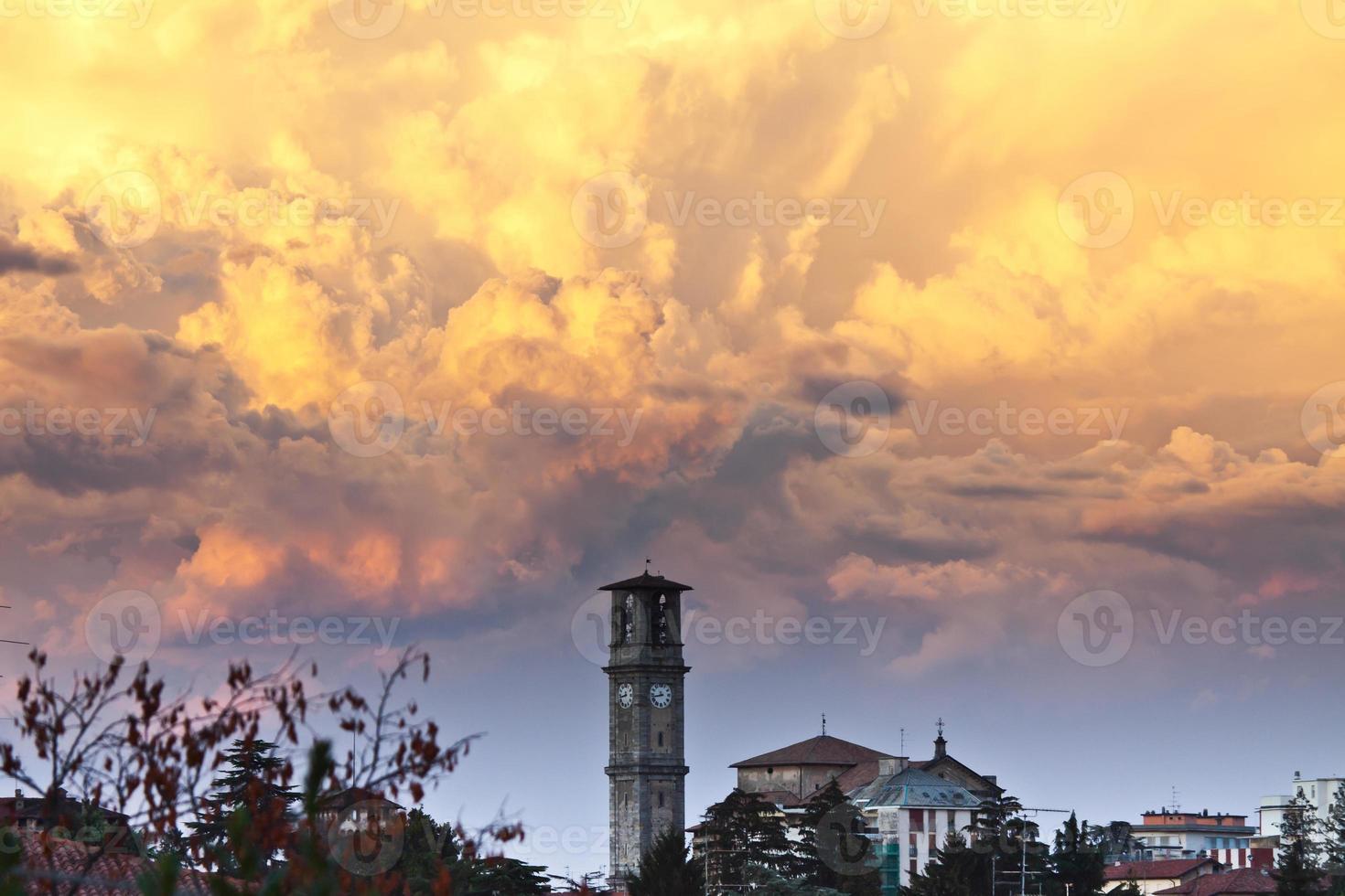 Tormenta vespertina con nubes contra la torre de campanas foto