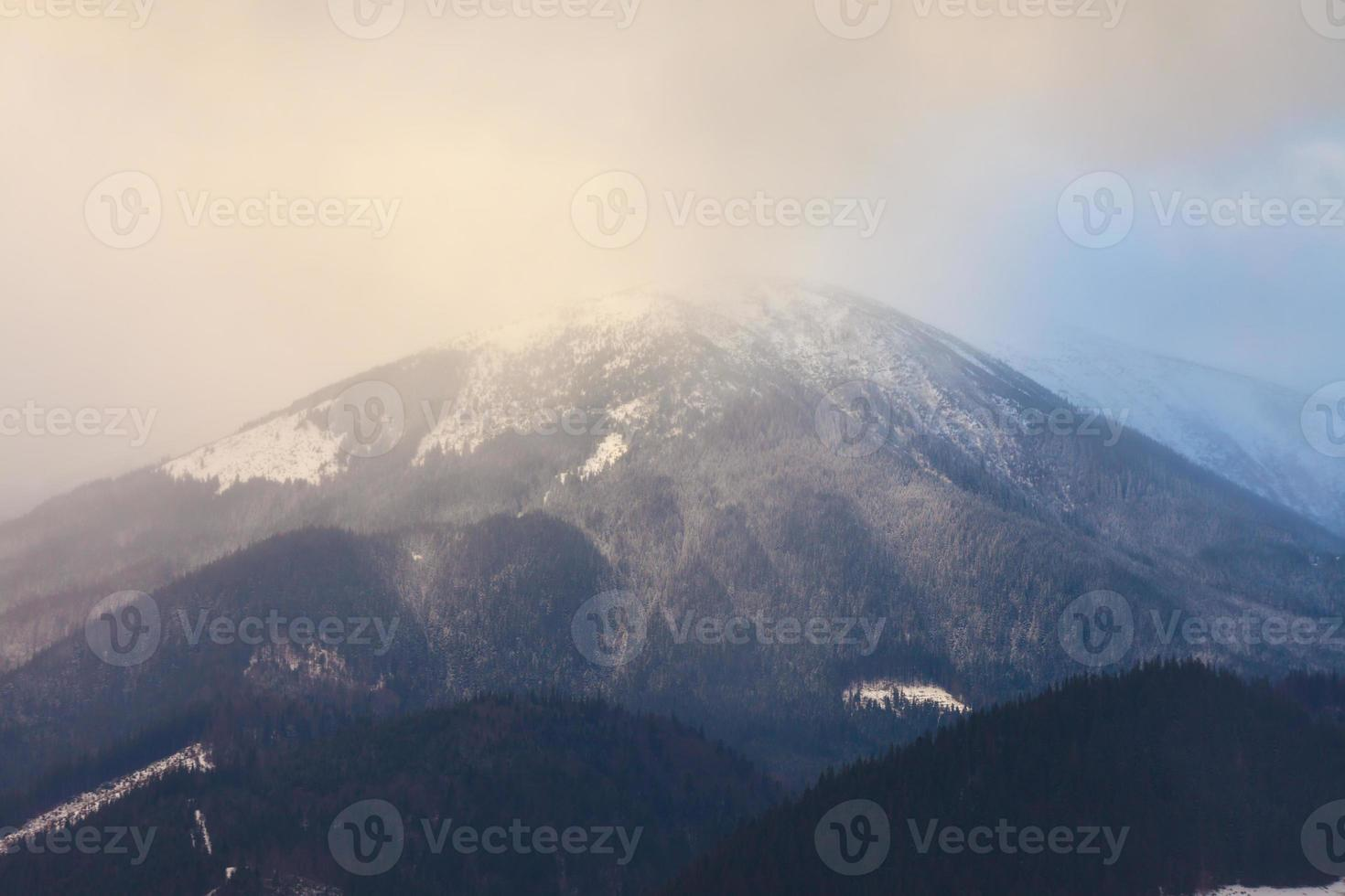 zonsondergang in de winterbergen met dramatisch licht foto