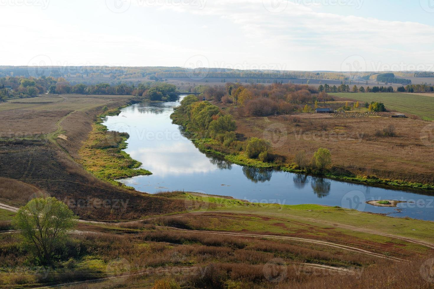 Campos de otoño y río estrecho con reflejos de nubes. foto