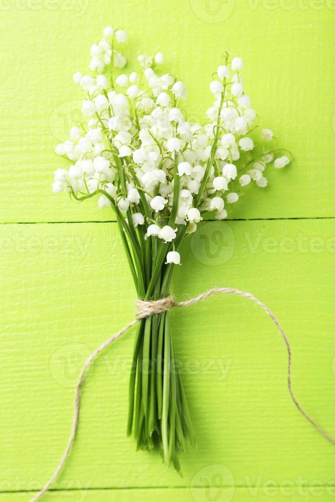 Lily of the Valley on green wooden background photo