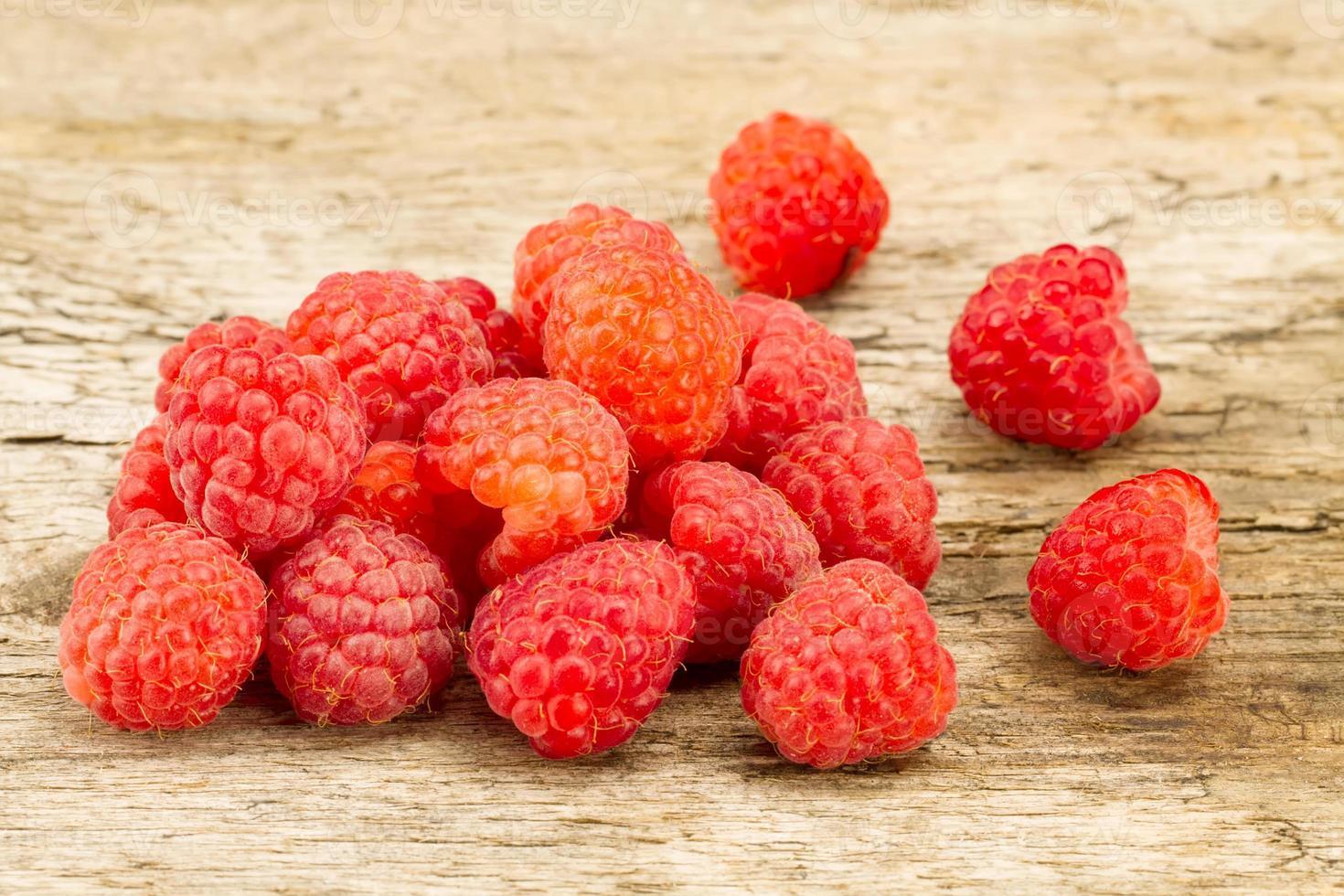 ripe raspberries closeup on wooden background photo