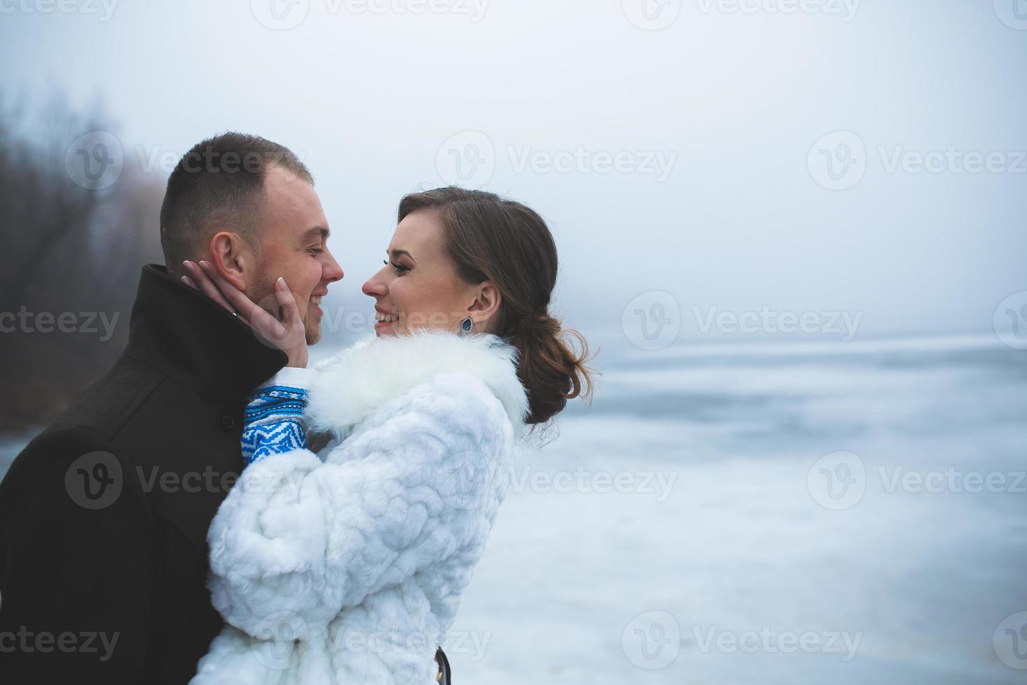 Beautiful couple on the dock in the winter fog. photo