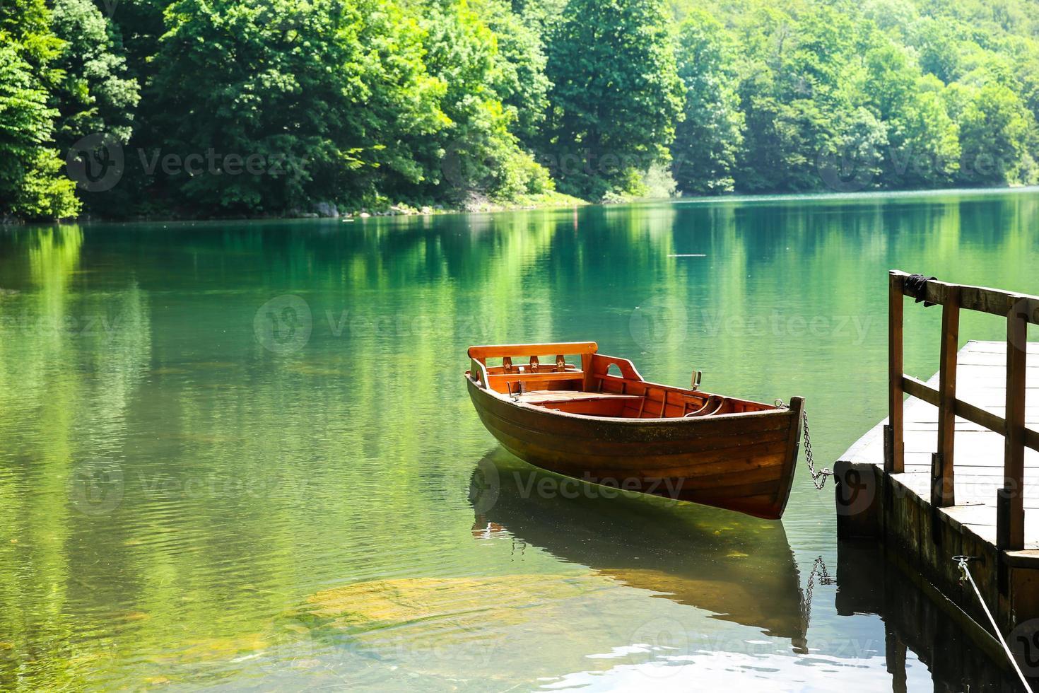 Wooden boat on mountain lake photo