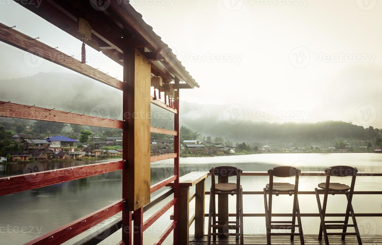 Tres sillas de bambú en un hermoso lago por la mañana. foto