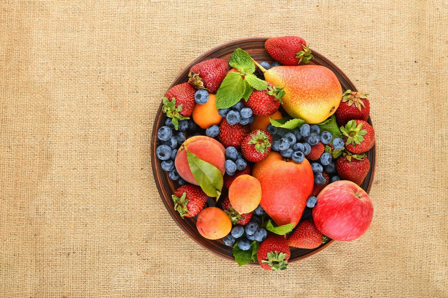 Fruits and berries mix in ceramic plate on burlap canvas photo