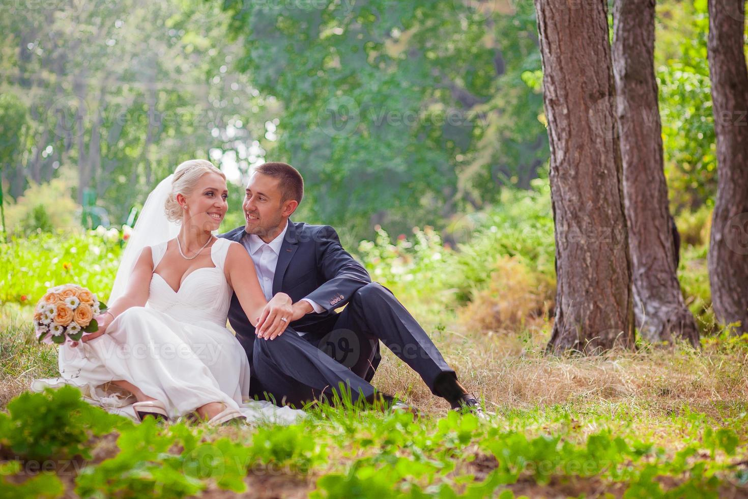 the bride and groom resting on grass in park photo