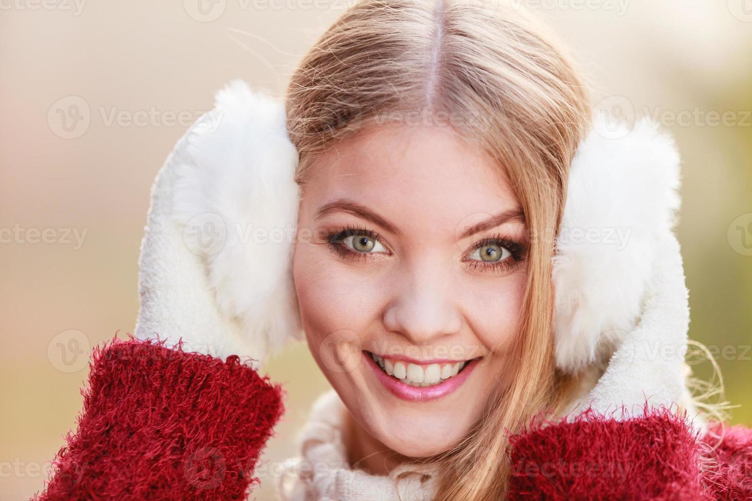 retrato de mujer muy sonriente en orejeras blancas. foto