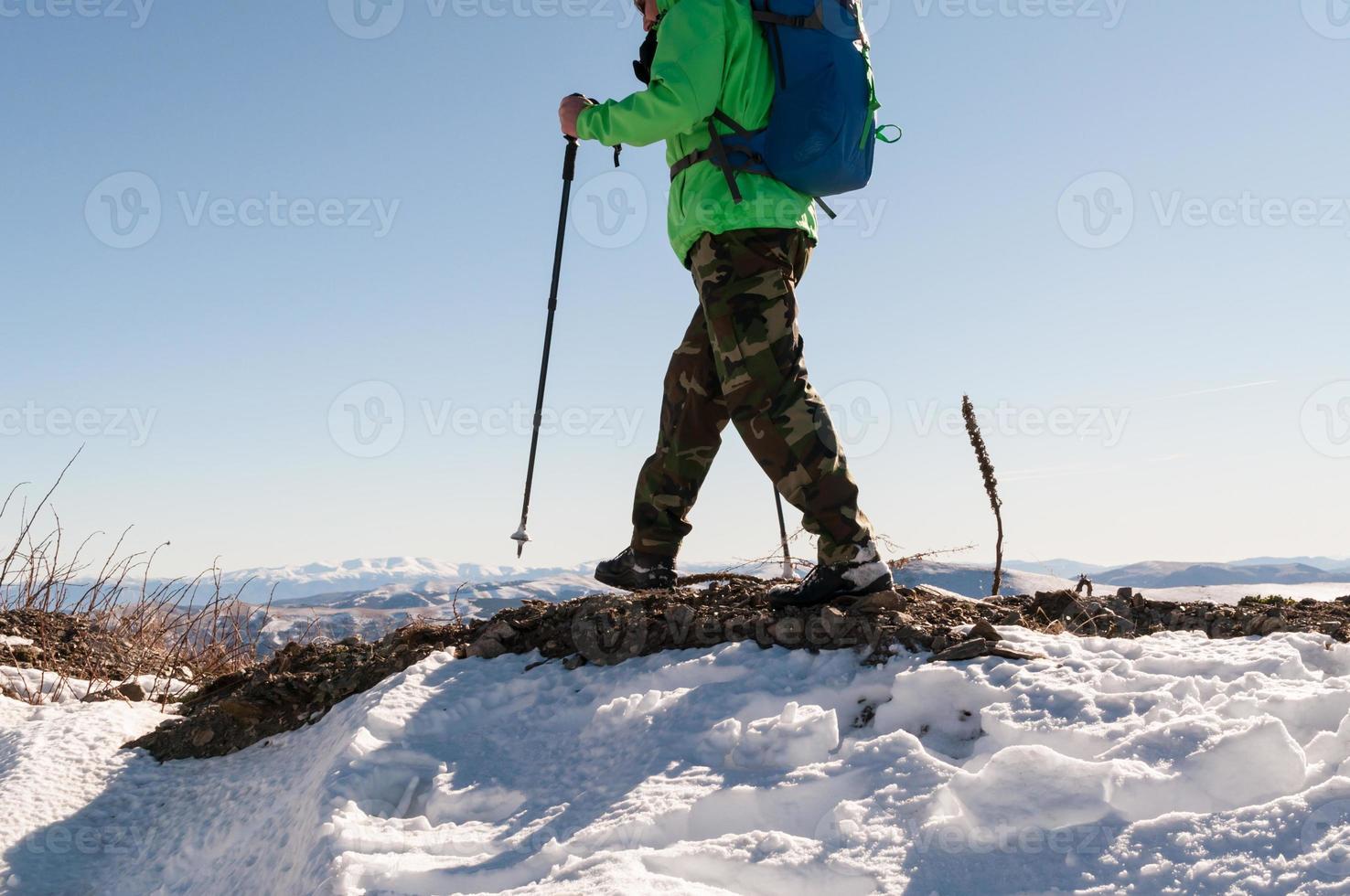 Backpacker walking on mountain peak photo