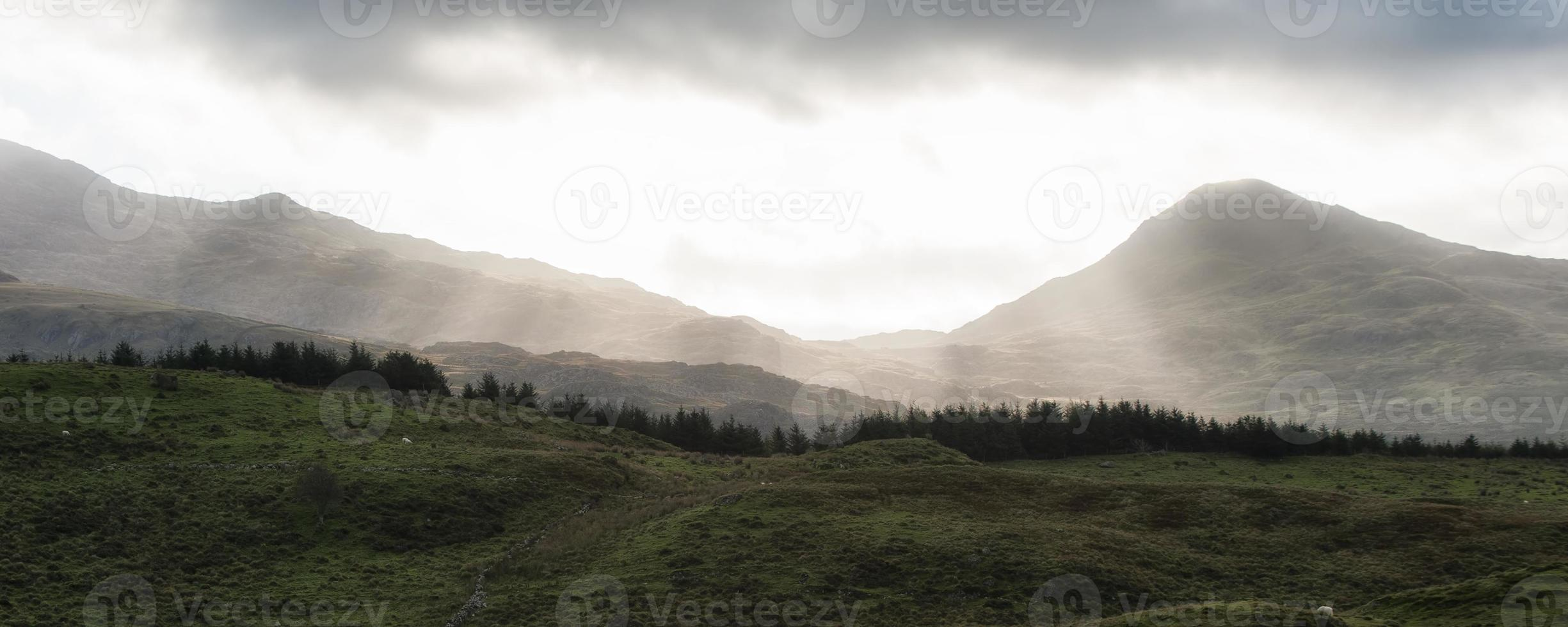 Panorama landscape sunrise over distant misty mountains with sun beams photo