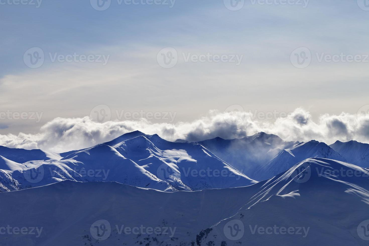 Evening winter mountains and sunlight clouds photo