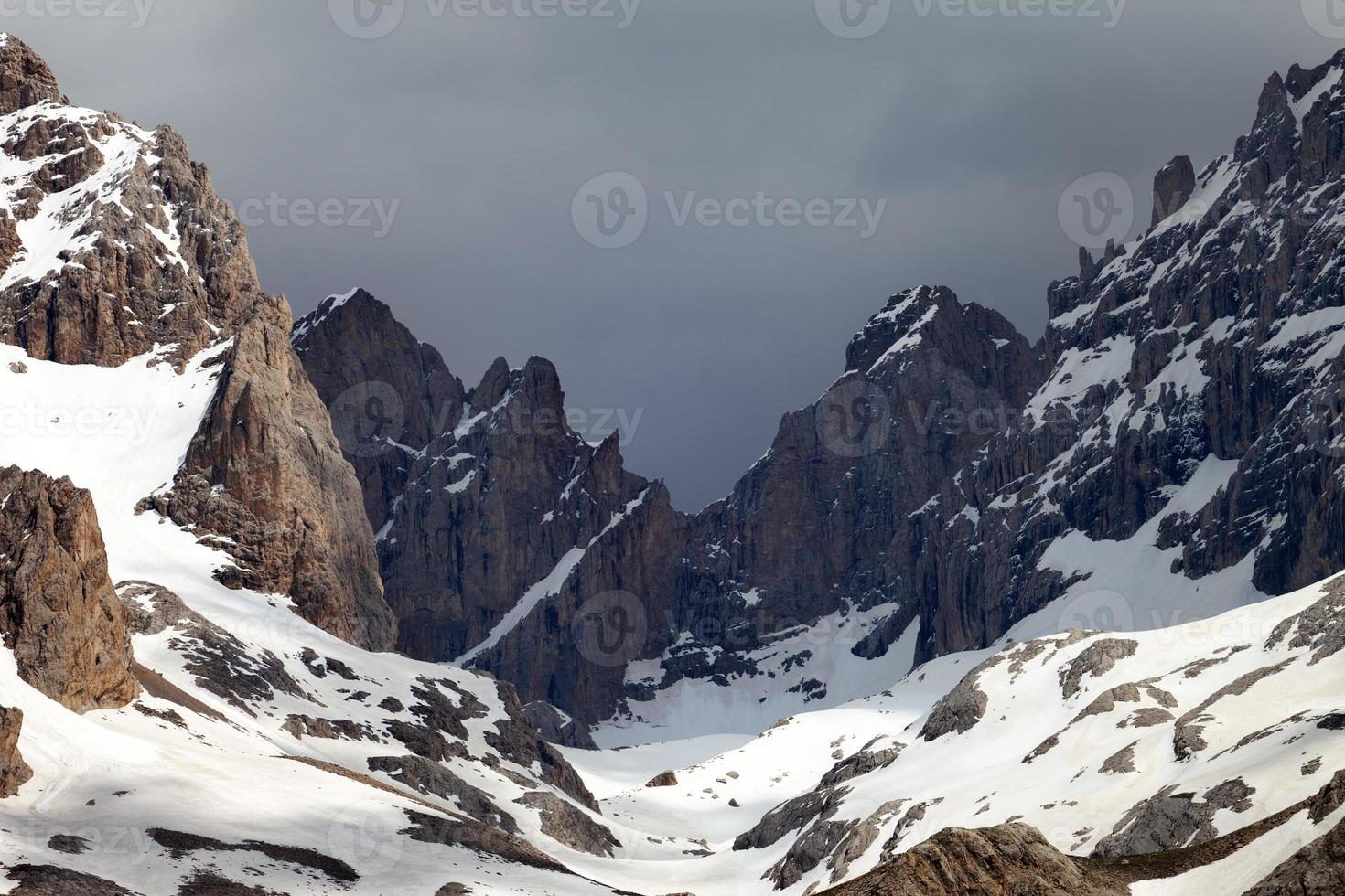 Snowy mountains and storm clouds photo