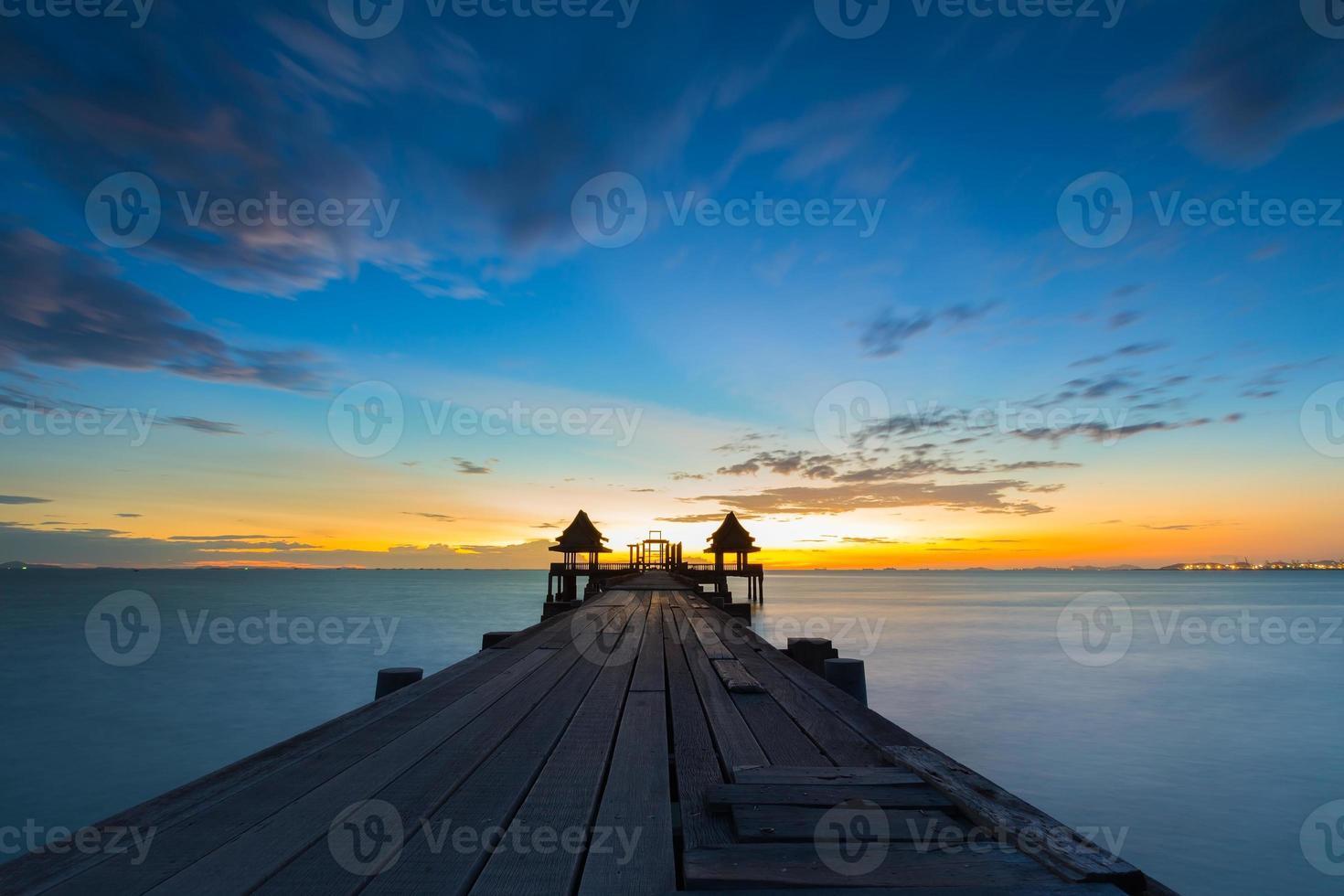 Old bridge on sea in sunset with beautiful sky photo