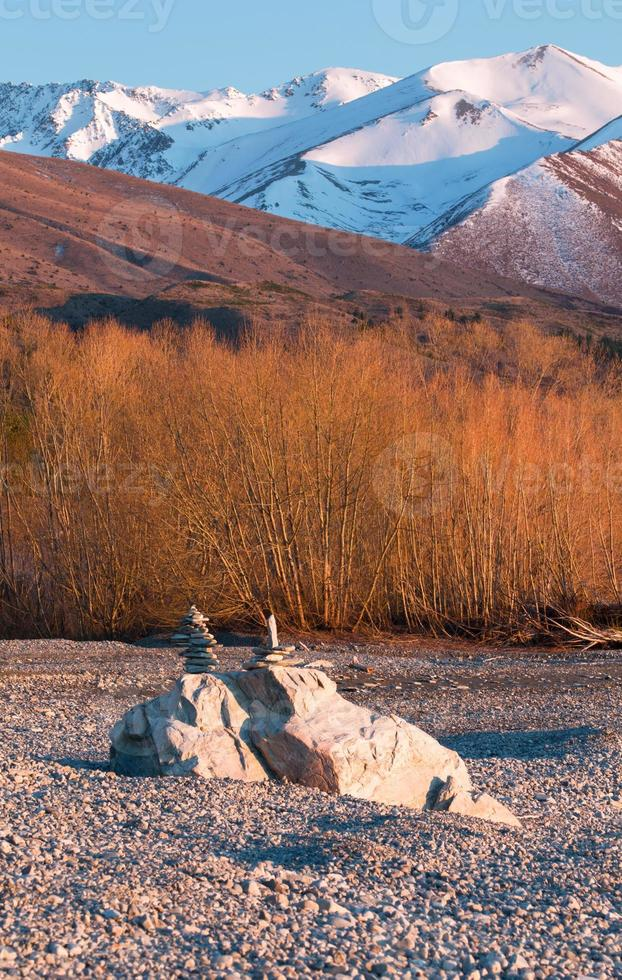 Balancing rocks on background of yellow willow trees photo