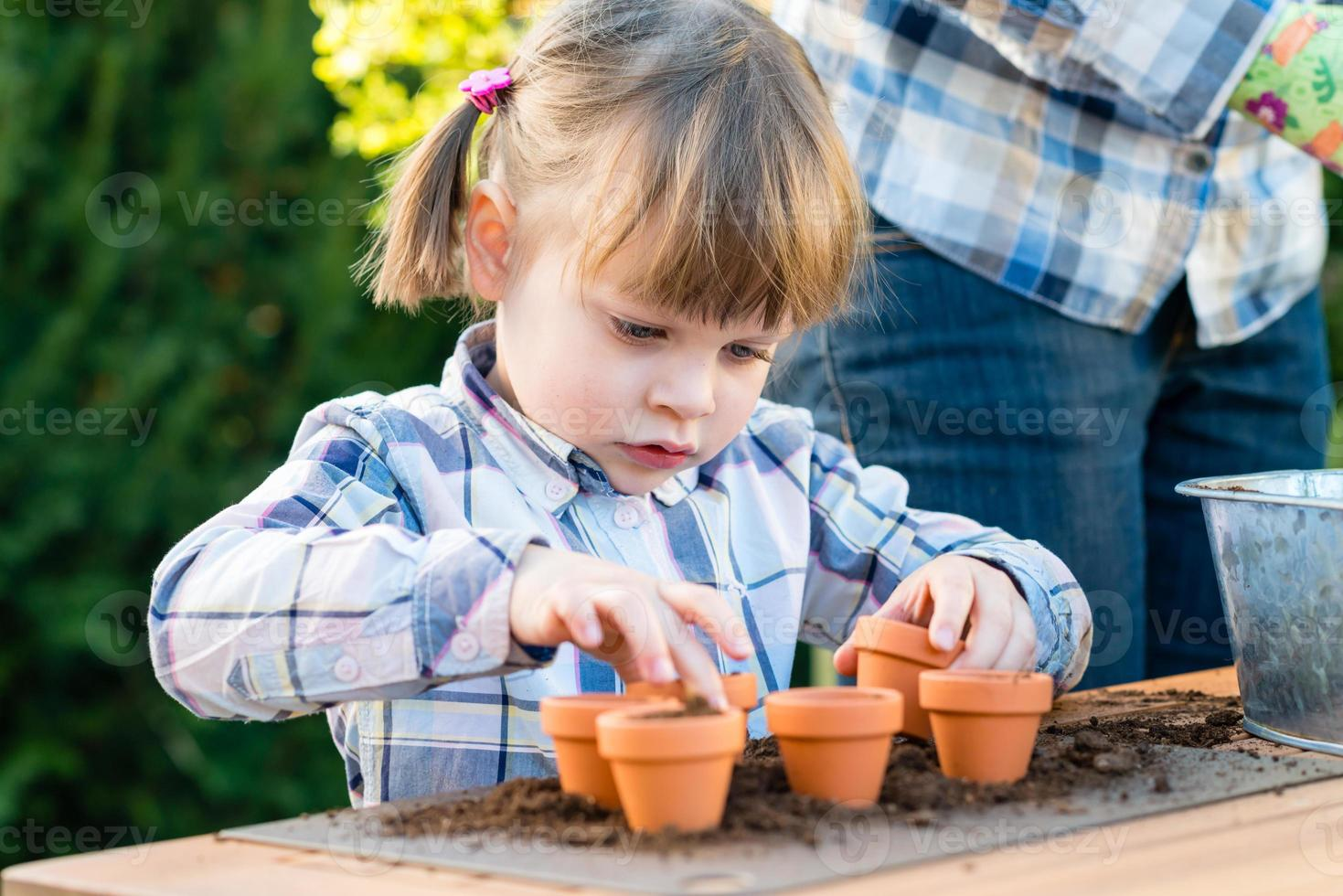Girl planting flower bulbs with her mother photo