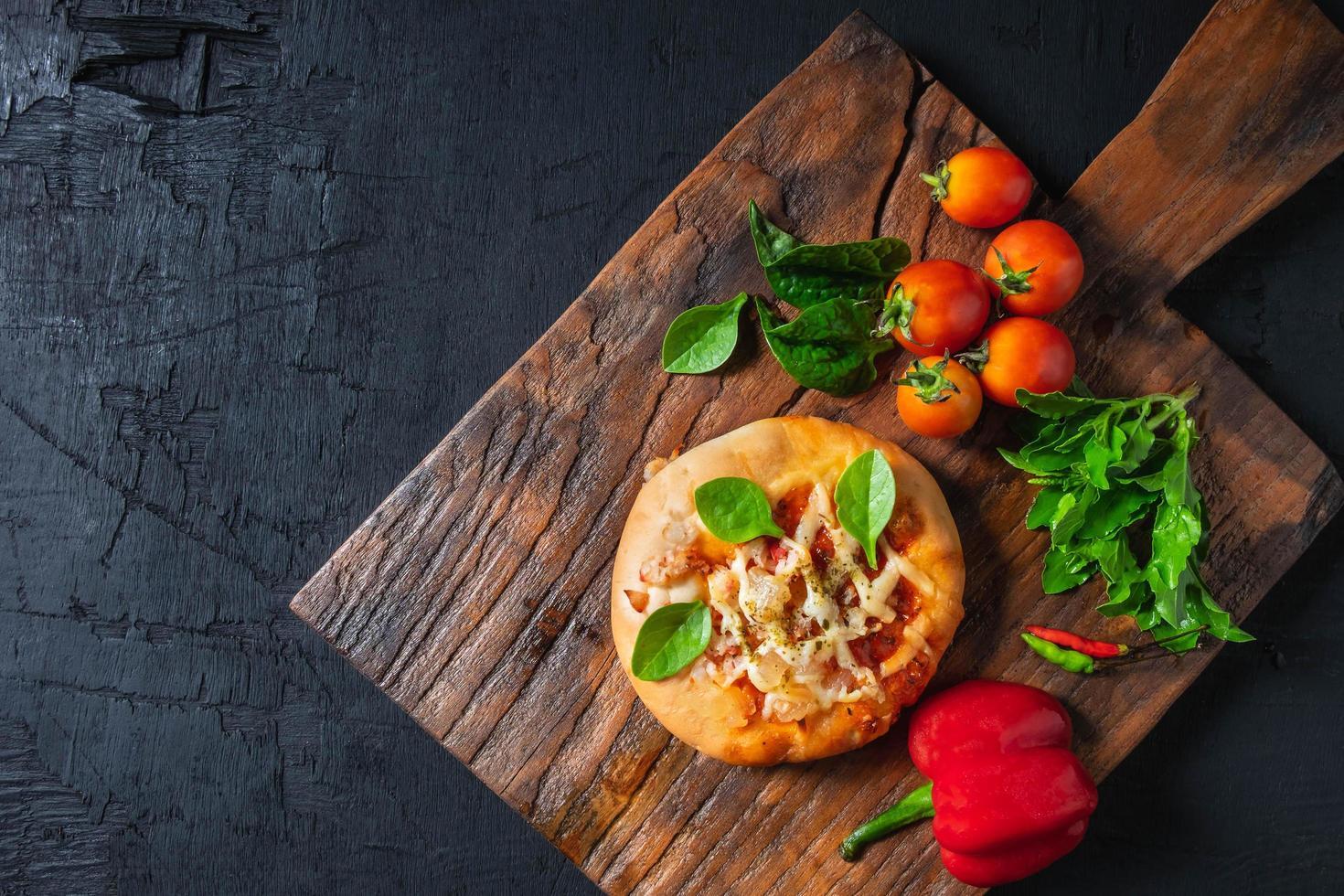 pizza en tablero de pizza de madera foto