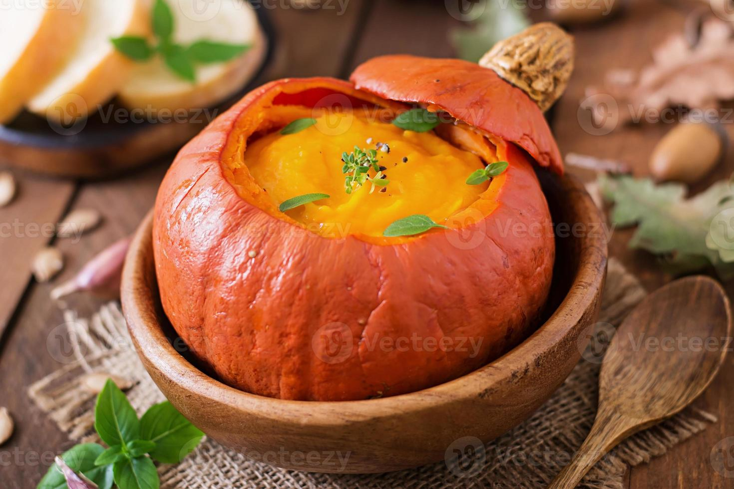 Pumpkin cream soup with peppers and herbs in a pumpkin photo