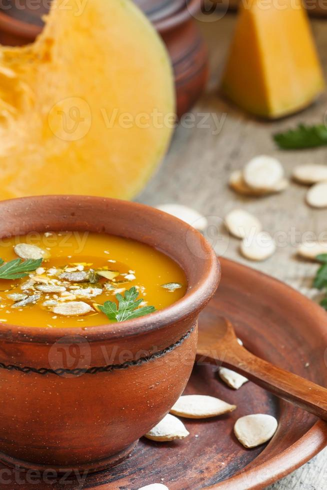 Pumpkin soup with oil and seeds in a clay bowl photo
