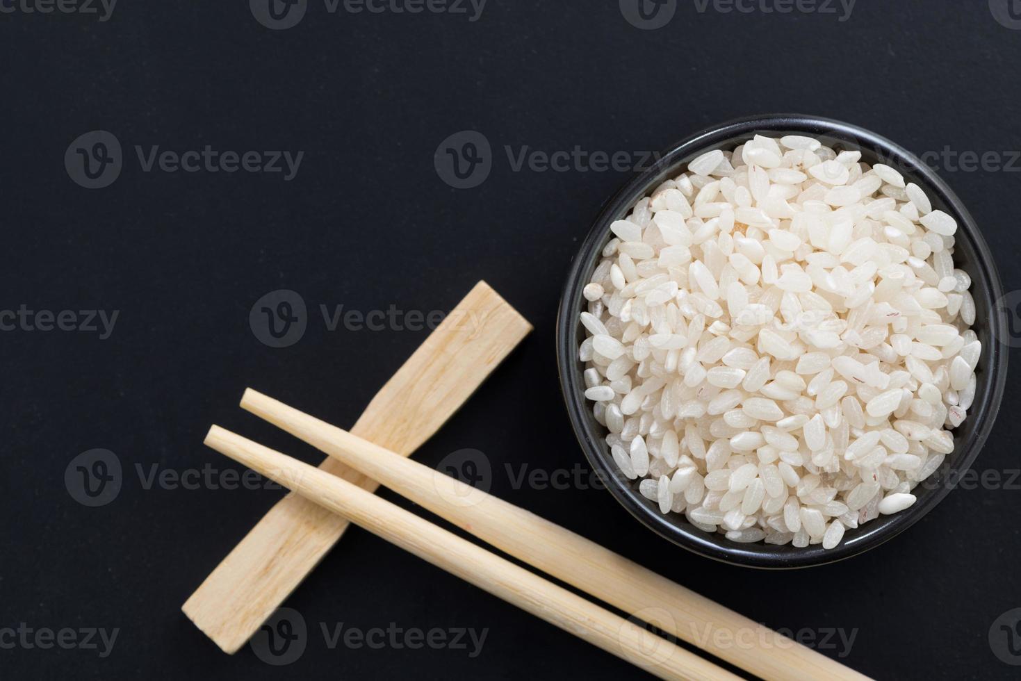 riz et baguettes pour sushi sur fond noir, vue du dessus photo