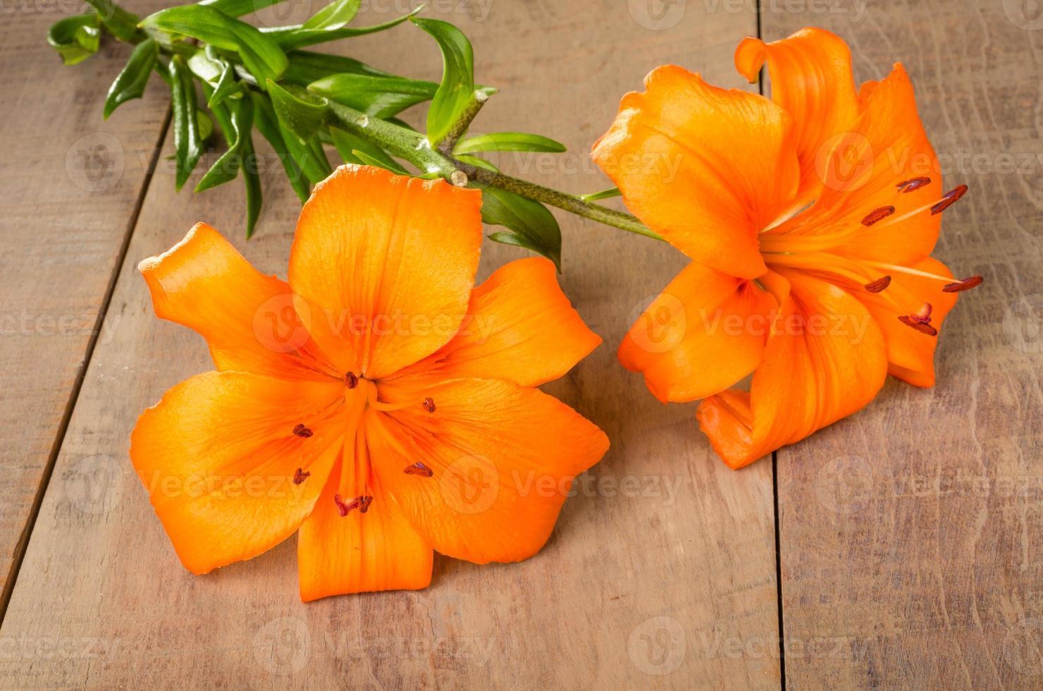 Flores de lirio naranja sobre una mesa de madera foto