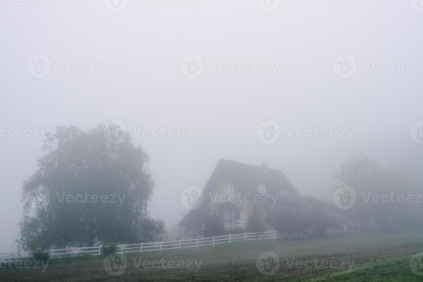 granja de niebla con valla blanca temprano en la mañana. foto
