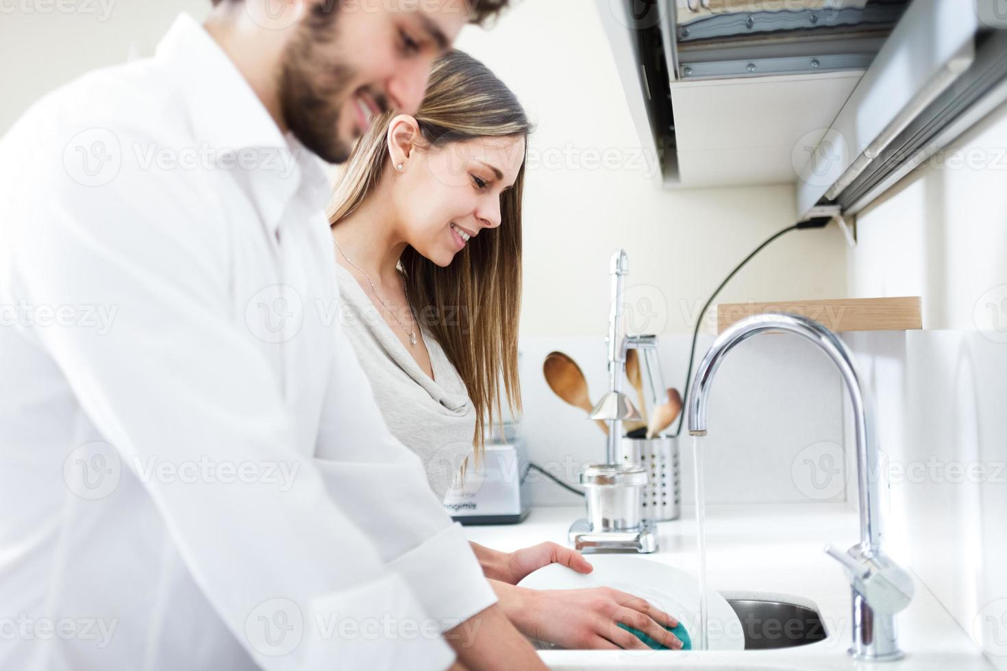 pareja joven lavando platos foto