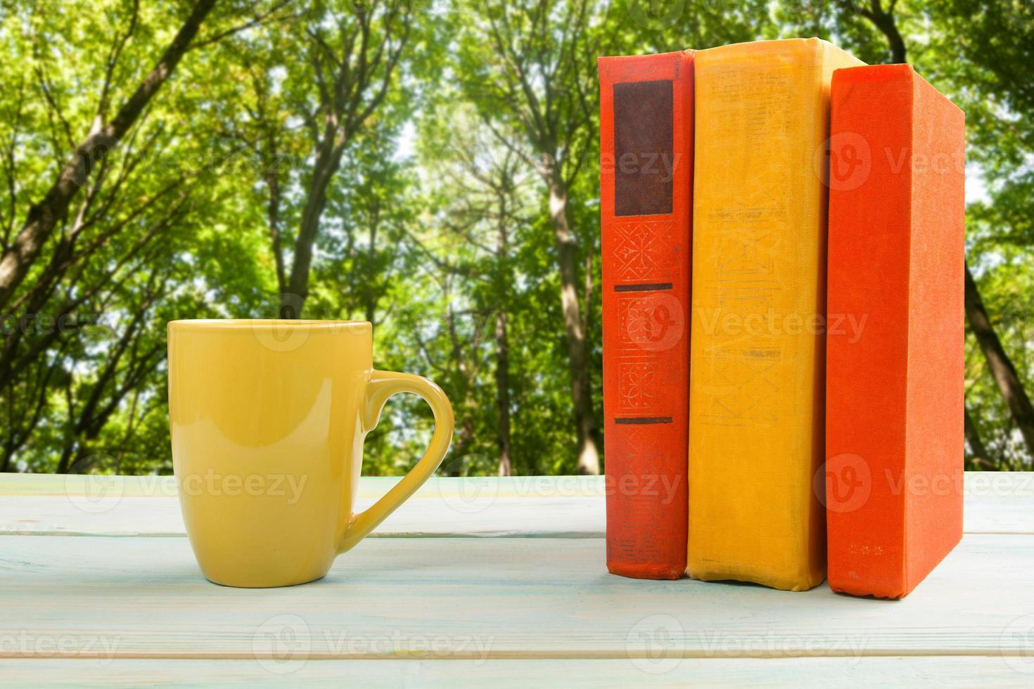 Stack of colorful books and cup on wooden table photo